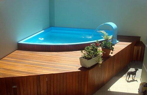 49 – Área de lazer com piscina em fibra de vidro de canto, deck em madeira