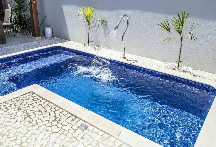 56 – Área de lazer com piscina em alvenaria em L. Bordas em mármore, fonte em inox