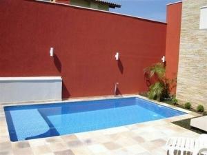 60 – Área de lazer com piscina em alvenaria e vinil. Piso em pedra São Tomé