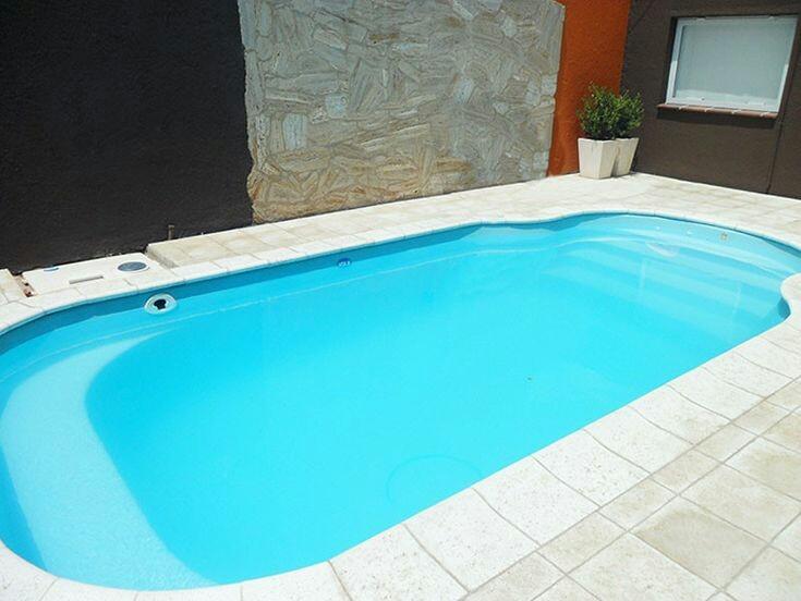61 – Área de lazer com piscina em fibra de vidro. Piso em pedra São Tomé