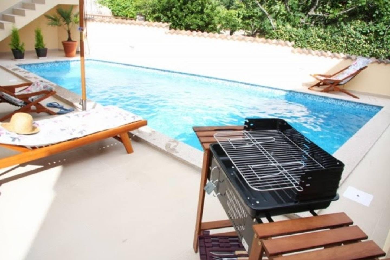 espaço de lazer com churrasqueira e piscina