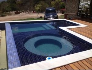 Foto 01 – Piscina em alvenaria, formato em L com escada interna e hidro redonda integrada a piscina.