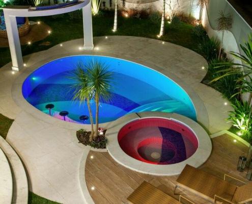 Piscina em alvenaria, com acabamento em pastilhas azuis, em linhas curvas, com bar molhado, escadas internas e hidro destacada com acabamento em pastilhas vermelhas.