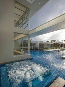 Foto 27 - Piscina grande alvenaria e formato geométrico que lembra uma cruz, com hidro em vidro, integrada e que se destaca na piscina com cascata que cai de uma viga que passa por cima da piscina.