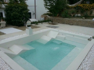 Foto 21 - Piscina quadrada em fibra de vidro, com espreguiçadeiras e hidro integrada e cascata em inox saindo do piso.