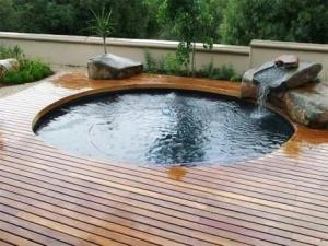 Foto 12- Piscina em alvenaria, redonda com hidro integrada, com cascata e deck em madeira.