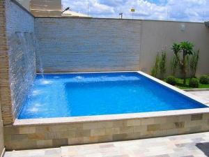 Foto 26 – Piscina quadrada elevada em alvenaria, com hidro integrada, parede com cascata.