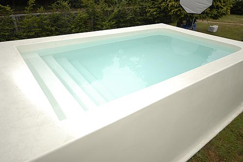 Modelo 49 - Piscina em fibra de vidro branca elevada, com deck e escadas internas.