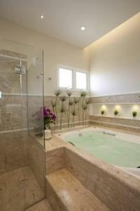 01 - Banheiro com banheira de hidromassagem retangular, box separado e acabamento em granito.