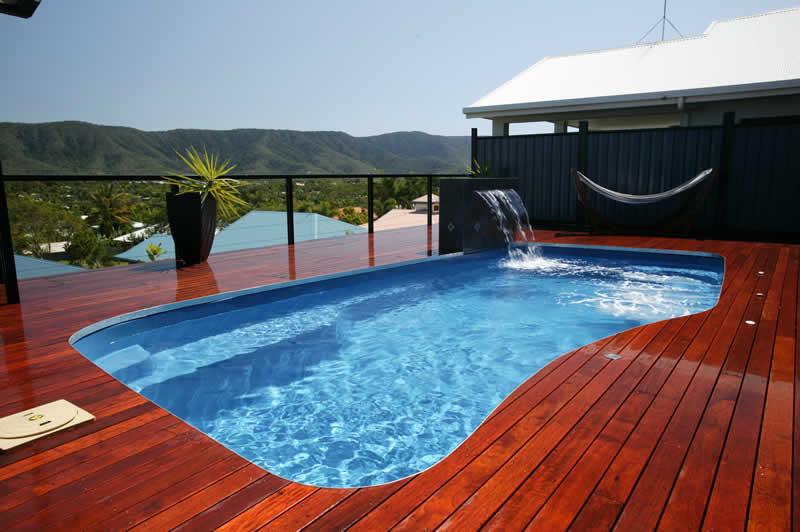 Piscina em fibra de vidro com deck de madeira e cascata de madeira