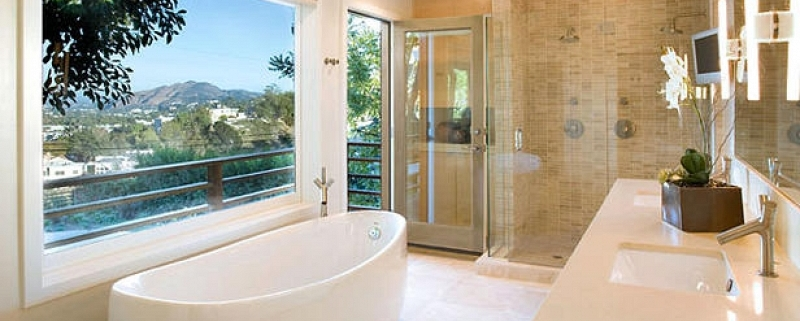 Banheiro com pia dupla de quartzo, banheira de imersão minimalista e ducha dupla separada.