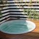 Piscina em fibra de vidro redonda em deck de madeira, com jardim suspenso em parede de madeira branca.